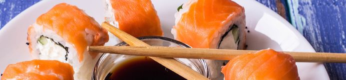 Banner of Philadelphia Maki Sushi made of Fresh Raw Salmon, Cream Cheese and Cucumber. With soy sauce Royalty Free Stock Images