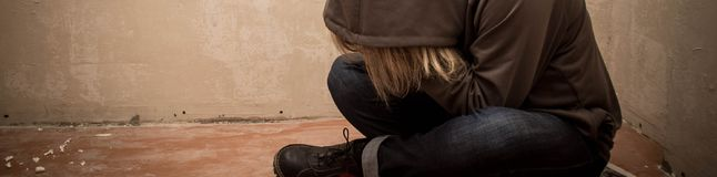Banner of Portrait of man sad, drug addict man sitting on the floor in corner.  Royalty Free Stock Photos