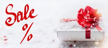 Banner with red Sale % text lettering, white gift box, red bow on snow with bokeh and snowfall. Valentines day coupon, sale and. Shopping concept royalty free stock images