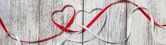 Banner of Red and white ribbon hearts for valentines day on wooden background.  stock images