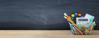 Banner of Shopping cart with school supply in front of blackboard. Back to school concept. stock photo