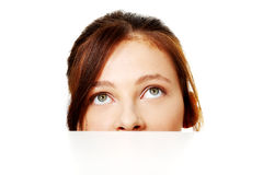 Banner sign woman. Peeking over edge of blank empty paper billboard Stock Photography