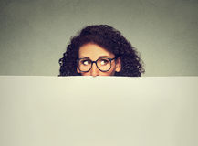 Banner sign woman peeking over edge of blank empty billboard with copy space for text Stock Photos