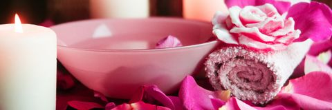 Banner Spa settings with roses. Fresh roses and rose petals in a bowl of water and various items used in spa treatments stock images