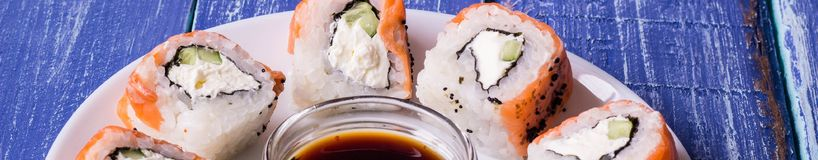 Banner of Sushi made of Fresh Raw Salmon, Cream Cheese and Cucumber. With soy sauce Royalty Free Stock Photo