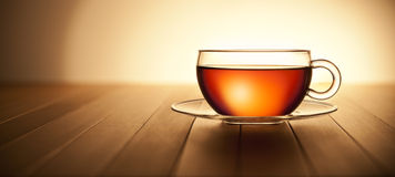 Banner Tea Cup Wood Background. A glass cup of tea on a warm wood background with a horizon Stock Photos