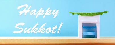 banner Tekst van Gelukkige Sukkot Een hut van document wordt met bladeren op een blauwe achtergrond wordt behandeld gemaakt die P stock foto