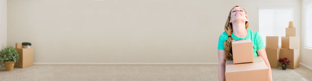 Banner of Tired Young Adult Woman Holding Moving Boxes In Empty Stock Images