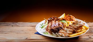 Banner with traditional Greek mixed grill platter. Banner with a traditional Greek mixed grill platter served with tomato rice, French Fries and cool refreshing stock photography