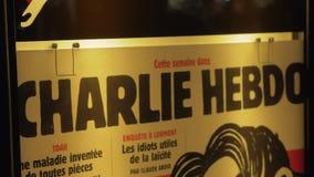Banner van het satirische tijdschrift van Charlie Hebdo in nachtstraat van Parijs, Frankrijk stock footage