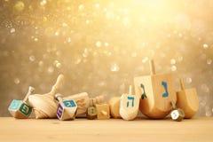 Banner van Joodse vakantiechanoeka met houten dreidels & x28; het spinnen top& x29; over schitter glanzende achtergrond vector illustratie