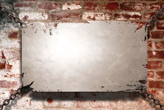 Banner and wall. A metal banner held with chains on a brick wall - room for copy on the banner Royalty Free Stock Photo