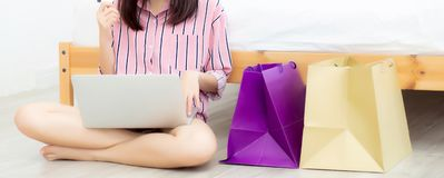 Banner website beautiful asian woman shopping online with laptop computer sitting on floor on room. Girl holding credit card purchase and shopping bags stock photos