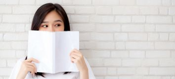 Banner website beautiful portrait asian woman happy hiding behind open the book with cement or concrete background, girl standing. Reading for learning stock image