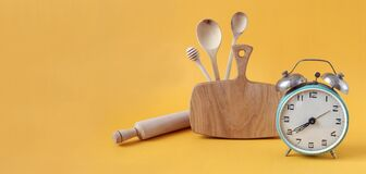 Banner :wooden kitchen utensils-board, spoons, rolling pin, alarm clock on a yellow background, side view, space for text