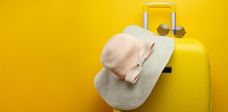 Banner yellow suitcase, with a hat for recreation, the beach and sunglasses. Travel Things Concept Festive Adventure Travel, on. Yellow background stock photo