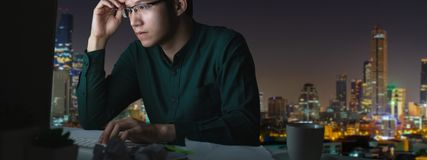 Banner of young asian man sitting on desk table work late and hard with computer laptop at office with night light city view. Background in noir concept smart stock images