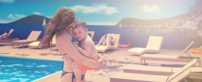 Banner Young mom holding a baby relaxing by the pool shines the bright sun Summer season family vacation travel royalty free stock photos