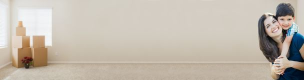 Banner of Young Mother and Son Inside Empty Room with Moving Boxes. Young Mother and Son Inside Empty Room with Moving Boxes Banner stock photo