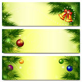 Banners with Christmas tree, bells and balls. Set of horizontal Christmas backgrounds with branches of spruce, balls and bells on light yellow background. Vector Stock Photography