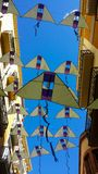Banners in the form of yellow kites against a bright blue sky, Reus, Spain. Stretched between tall houses stock images