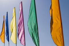 Banners In The Wind. A row of brightly colored banners waving in a brisk wind are highlighted against a blue sky royalty free stock photo