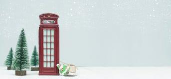 Bannière avec des décorations de Noël, cabine de téléphone rouge de jouet, arbres, g photo stock