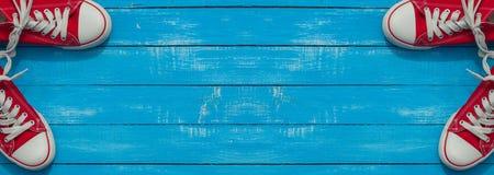 Bannière avec deux paires de chaussure rouge de la jeunesse sur une surface en bois bleue Image libre de droits