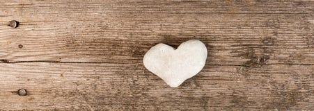 Bannière avec un coeur de pierre sur le fond en bois Image stock