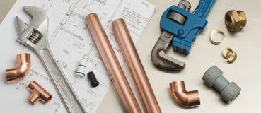 Bannière d'outils de plombiers et de matériaux de tuyauterie sur des plans de Chambre photographie stock