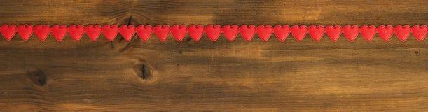Bannière de jour du ` s de Valentine, coeurs rouges sur le bois Photos libres de droits
