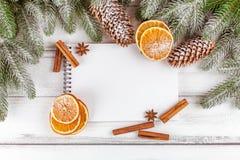 Bannière de Noël avec l'arbre, les cônes, l'orange, la cannelle et le carnet verts sur le fond en bois blanc Photo libre de droits