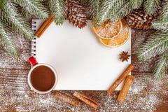 Bannière de Noël avec l'arbre vert, les cônes, les tasses rouges avec du chocolat chaud, l'orange et la cannelle sur le fond en b Photos stock