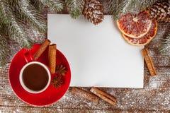 Bannière de Noël avec l'arbre vert, les cônes, les tasses rouges avec du chocolat chaud, l'orange et la cannelle sur le fond en b Image libre de droits