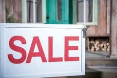 Bannière de vente avec des clés se tenant près de la nouvelle maison, maison à vendre le concept Images stock