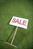 Bannière de vente se trouvant sur l'herbe verte, maison à vendre le concept Images stock