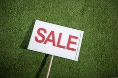 Bannière de vente se trouvant sur l'herbe verte, maison à vendre le concept Photo stock