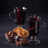 Bannière de vin chaud Verres avec le vin rouge et les épices chauds sur le fond foncé Style foncé moderne d'humeur Image stock