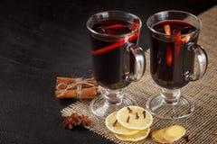 Bannière de vin chaud Verres avec le vin rouge et les épices chauds sur le fond foncé Style foncé moderne d'humeur Photographie stock