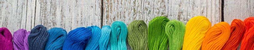 Bannière des fils de couture colorés pour la broderie sur le fond en bois blanc Photo stock
