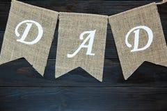 Bannière heureuse de jour de pères sur le fond en bois de cru brun le papa de mot wriiten sur les drapeaux images libres de droits
