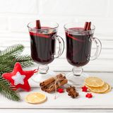 Bannière horizontale de vin chaud d'hiver Verres avec le vin rouge et les épices chauds, arbre, décorations de feutre sur le fond Photographie stock