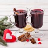 Bannière horizontale de vin chaud d'hiver Verres avec le vin rouge et les épices chauds, arbre, décorations de feutre sur le fond Photo stock
