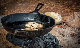 Bannock som lagar mat över en öppen brand i brandgrop Arkivfoto