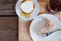 Banoffee kaka, en kopp kaffe och ett exponeringsglas av lemontea Arkivfoto