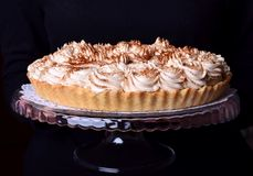 Banoffee pie topped with whipped cream and sprinkled with ground coffee on a glass stand. In female hands stock photo