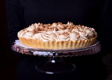 Banoffee pie topped with whipped cream and sprinkled with grounded coffee. On a glass stand in female hands royalty free stock images