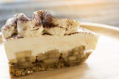 Banoffee-Torte mit Schokoladenpulver auf hölzerner Platte Lizenzfreies Stockbild