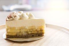 Banoffee-Torte mit Schokoladenpulver auf hölzerner Platte Stockfoto