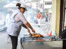 Ecuadorian woman preparing an Ecuadorian delicacy called lechon , bbq a small type of pig on grill. Banos, Ecuador - December 25th, 2017: Ecuadorian woman Stock Images